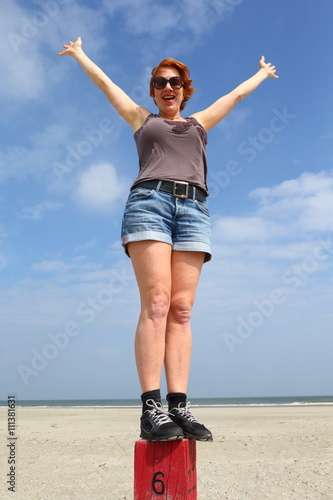 happiness/ woman standing on a a pole at the beach feeling happy Poster