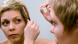 Pretty blond woman combs and brushes her hair