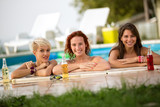 Female bathers standing in front of railing of pool with bottles