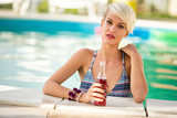 Blond woman standing near pool edge with refreshing drink