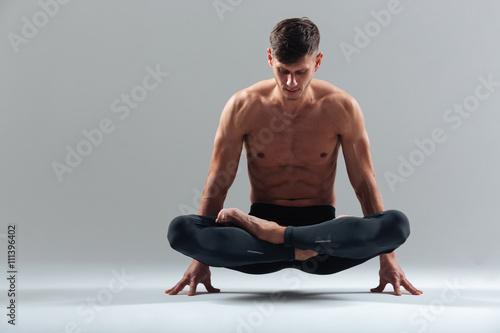 Fototapeta Przystojny mężczyzna robi ćwiczenia jogi
