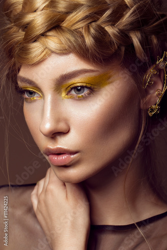 Póster Beautiful girl in a gold dress with creative makeup and braids on her head