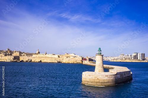 Fototapeta Valletta, Malta - old Lighthouse and Breakwater bridge in the morning with blue sky
