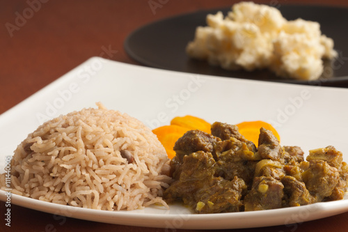 Curried Goat served with Rice & Peas, vegetables and homemade potato salad.