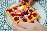 Freshly baked Belgian waffle with fresh fruit and berry coulis