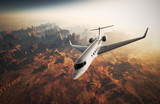 Fototapety Photo White Glossy Luxury Generic Design Private Jet Flying in Sky under Earth Surface.Grand Canyon Background Sunrise. Business Travel Picture.Horizontal,Top Angle View.Film Effect. 3D rendering.