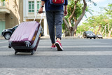 Cropped image of traveler with big suitcase crossing road