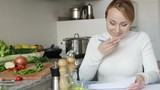 Happy woman sitting with financial papers in kitchen and smiling
