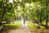 Young woman walking on path into an enchanted forest.