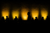 Silhouettes of people sitting in front of a wall lighted with co