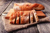 Freshly baked French baguette, sliced on a wooden board. In rustic style on sackcloth.