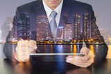 Double exposure of business man working with tablet, city, urban and lake at night as Communication and Technology concept.