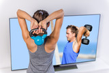 Fitness at home woman working out watching tv. Back of a young sporty girl following workout videos online on smart television, lifting kettlebell toning arms and shoulders exercising triceps.