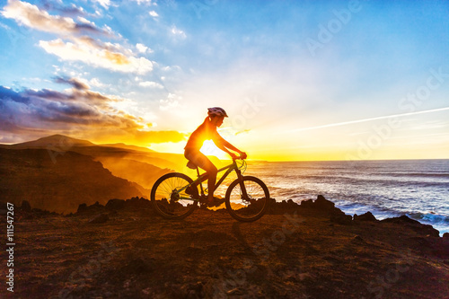 obraz PCV Mountain biking MTB cyclist woman cycling on bike trail on coast at sunset. Person on bike by sea in sportswear with bicycle enjoying healthy active lifestyle in beautiful nature.