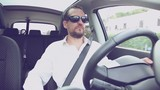 Serious man with white shirt driving car with sun glasses retro style