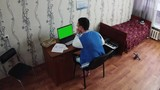 Young man sitting at notebook in dormitory room. Old bed with red blanket. Synthesizer. Student. Study