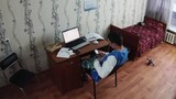 Young boy sitting at notebook in dormitory room. Old bed with red blanket. Take phone in hands. Student