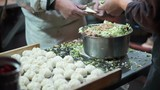 Hand made dumpling stuffing meat inside flour at night market street food stall