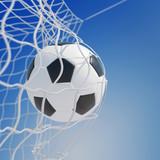 Piłka nożna w siatce z bramy przed niebem