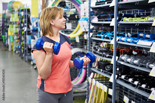 Woman chooses dumbbells for fitness in sports shop Poster