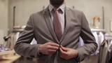 happy young man trying suit at clothing store