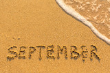 September - written by hand on a golden beach sand.