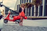 Blond kobiet w czerwonej spódnicy wychodzi z czerwonym skuterem.