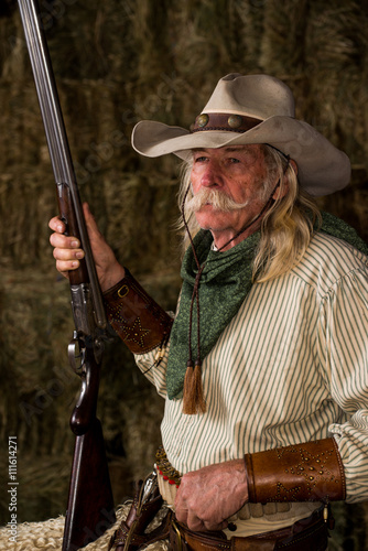 Authentic old west cowboy with shotgun, hat and bandanna in stable Poster