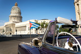 Cuban flag on a classic car with the Capitolio on the background in Havana, Cuba