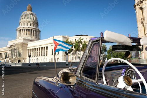 Cuban flag on a classic car with the Capitolio on the background in Havana, Cuba Poster