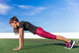 Fitness woman planking doing the bodyweight exercise for core strength training. Active girl practicing the yoga plank pose for abdominal muscles in summer outdoors living a fit life.