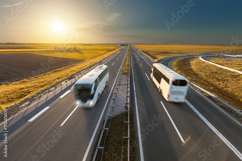 Poster Fast travel buses on the highway at idyllic sunset