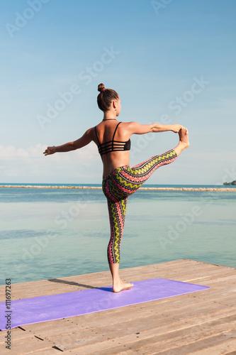 Poster Woman doing yoga in the morning at the sea.
