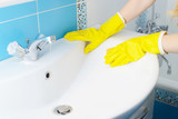 Cleaning - cleaning bathroom sink and faucet with detergent in yellow rubber gloves