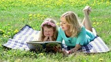 Beautiful woman and girl reading a book outdoors laying on a blanket in the grass.Panoramic camera movement.