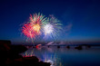 Colorful fireworks explode in a Maine harbor at dusk filled with boats.