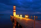 Leuchtturm mit beleuchteten Steg am See zur blauen Stunde