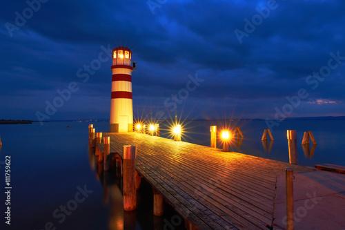 Leuchtturm mit beleuchteten Steg am See zur blauen Stunde - 111759622