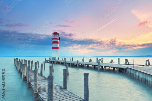 alter Holzsteg am See mit Leuchtturm zum Sonnenuntergang - 111759843