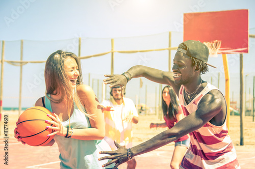 Group of multiracial happy teenagers playing basketball outdoors