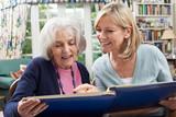 Senior Woman Looks At Photo Album With Mature Female Neighbor