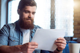 Pleasant bearded man working with papers