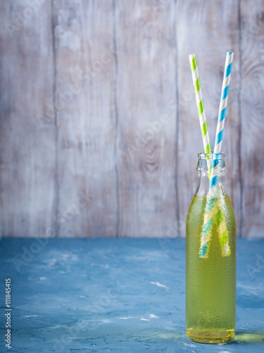Poster Lemon sparkling soft drink in a glass bottle with colored paper straws on wooden