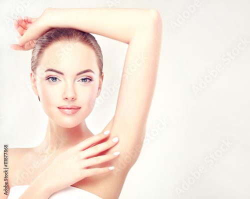 Fototapeta Armpit epilation, lacer hair removal. Young woman holding her arms up and showing underarms, armpit smooth clear skin .Girl showing clean armpit .Beauty portrait.Epilation and depilation of hair .