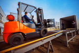 Fototapety Forklift is putting cargo from warehouse to truck outdoors