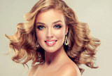 Fototapety Beautiful girl  blonde hair with an elegant hairstyle , hair wave ,curly hairstyle . Jewellery , earrings and bracelet