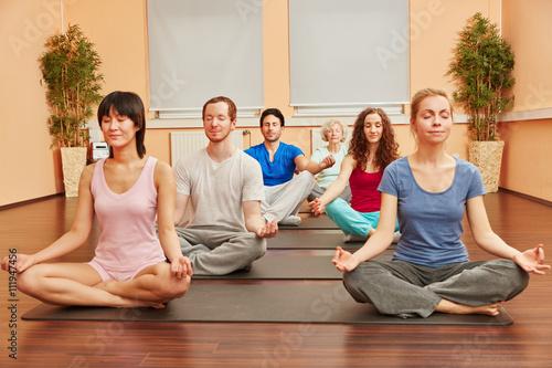 Gruppe im Yoga Kurs meditiert...