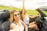 Couple of girls taking a selfie at car trip