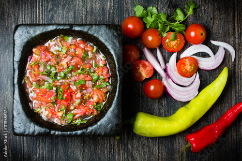 Plagát, Obraz Tomato sauce salsa and ingredients dark stone background.