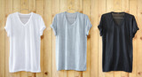 White T-shirt, Black T-shirt and Gray T-shirt hang on wood wall.